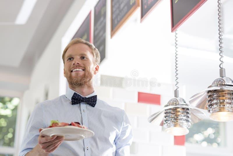 Camarero joven sonriente que celebra la placa de ensalada por las luces pendientes en el restaurante imágenes de archivo libres de regalías