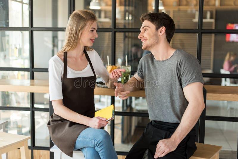 camarero joven y camarera que tienen conversación durante rotura en el trabajo fotos de archivo