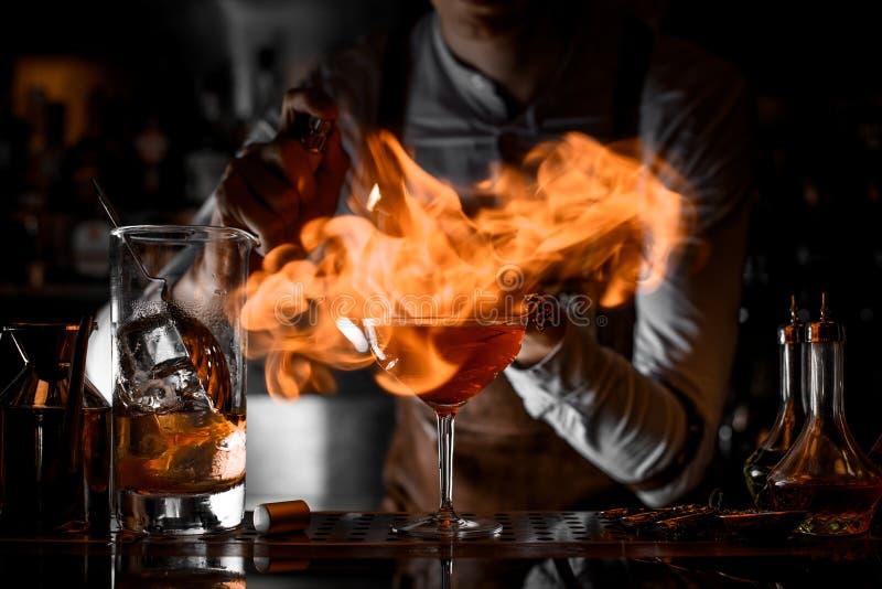 Camarero profesional que pone el fuego del encendedor en el vidrio de cóctel fotografía de archivo libre de regalías