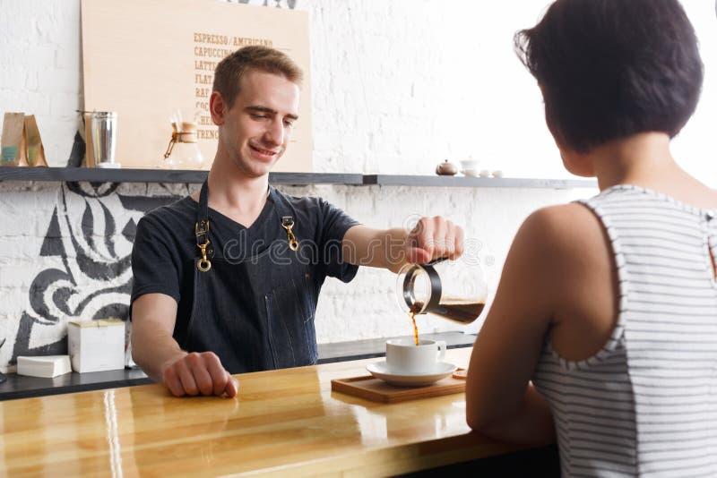 Camarero que charla con la huésped y el café de servicio fotos de archivo