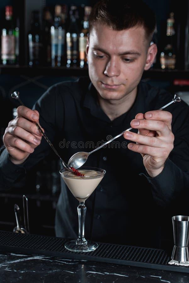 Camarero que hace el cóctel de Martini del café express, finishig añadiendo granos de la granada en el top Barra en un fondo fotos de archivo