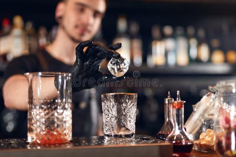 Camarero que hace el cóctel Vidrio de Putting Ice In del camarero foto de archivo libre de regalías