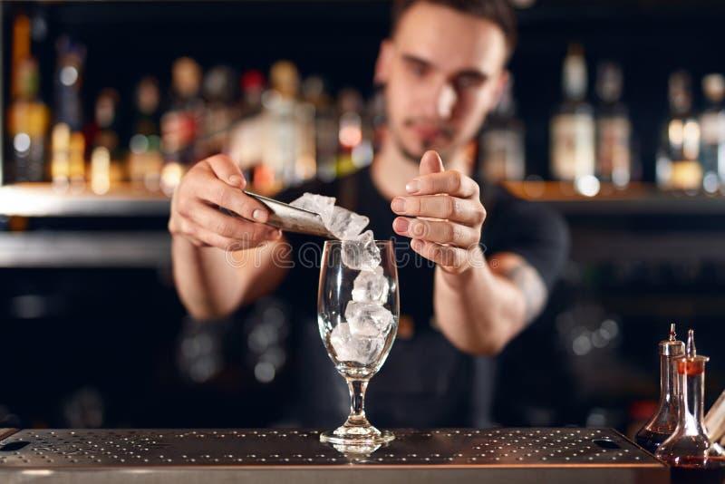 Camarero que hace el cóctel Vidrio de Putting Ice In del camarero imagen de archivo