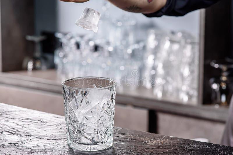 Camarero que hace el c?ctel Vidrio de Putting Ice In del camarero foto de archivo libre de regalías