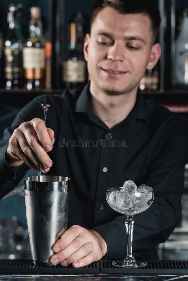 Camarero que hace el líquido de colada del cóctel de Boulevardier en el vidrio Barra en un fondo fotos de archivo