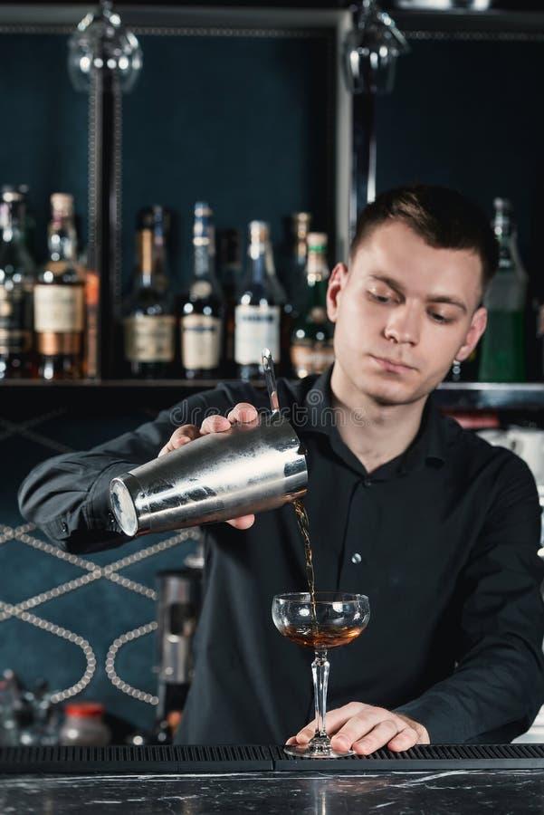 Camarero que hace el líquido de colada del cóctel de Boulevardier en el vidrio Barra en un fondo imagen de archivo libre de regalías