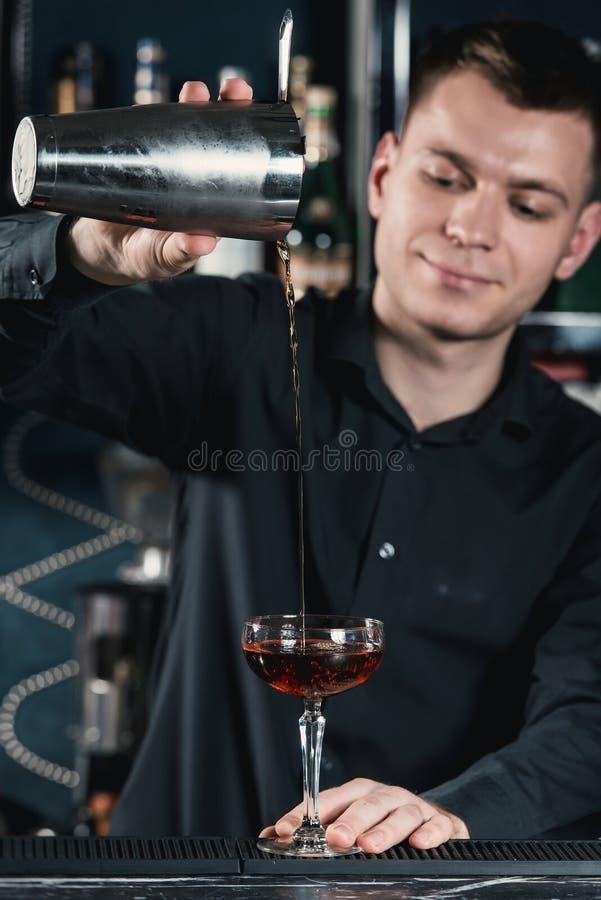 Camarero que hace el líquido de colada del cóctel de Boulevardier en el vidrio Barra en un fondo imagenes de archivo