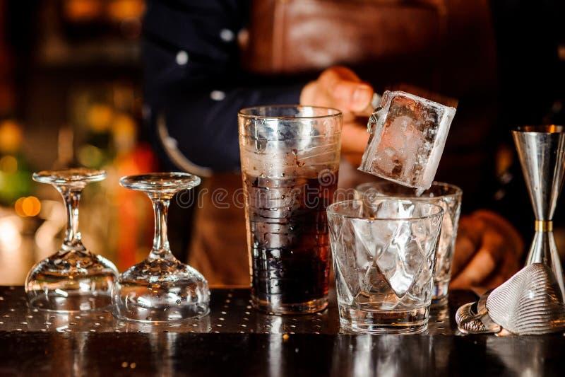 Camarero que hace un cóctel y que pone un cubo de hielo en el vidrio imagen de archivo