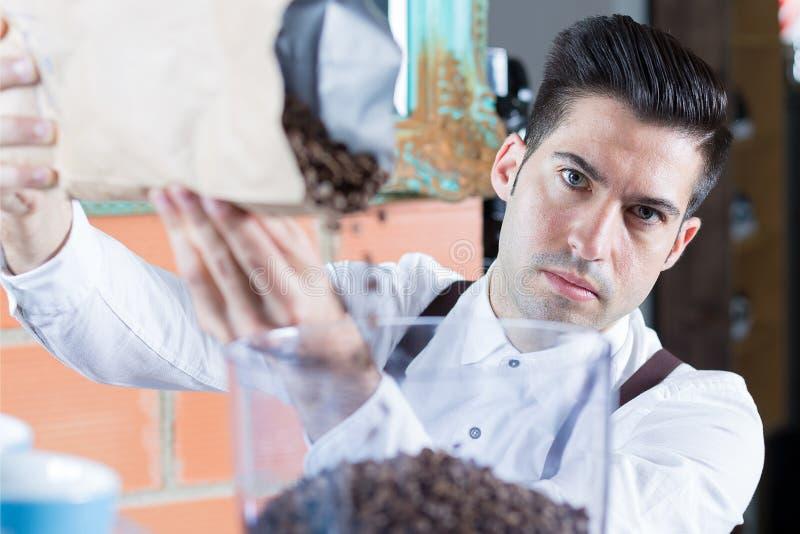 Camarero que llena encima de los granos de café y que mira la cámara imágenes de archivo libres de regalías
