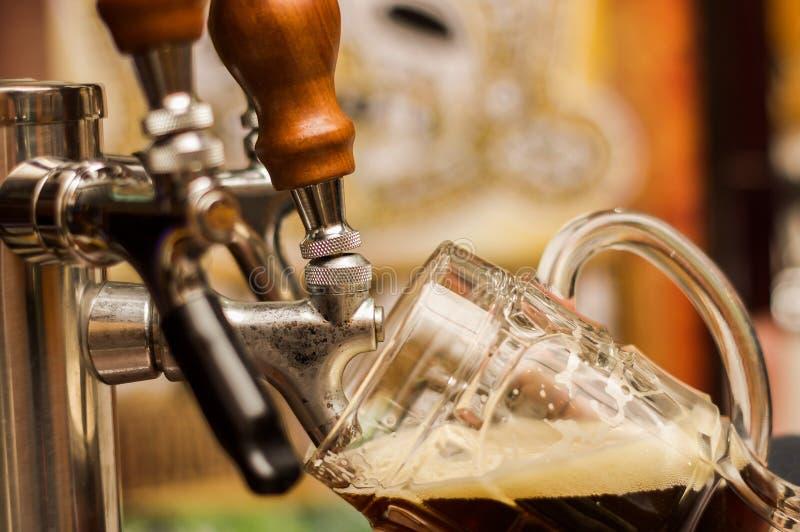 Camarero que llena encima de una oscuridad de la cerveza del arte al vidrio de la pinta imagen de archivo