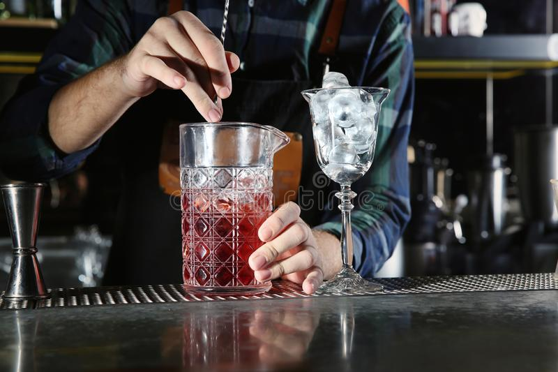Camarero que mezcla el cóctel alcohólico en el contador en club nocturno imagen de archivo libre de regalías