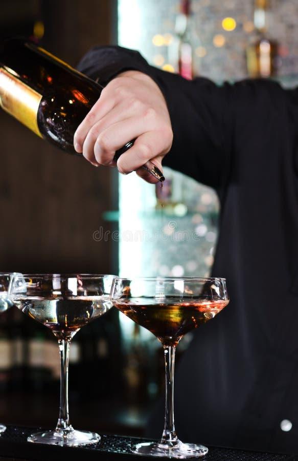 Camarero que mezcla los cócteles alcohólicos imagenes de archivo