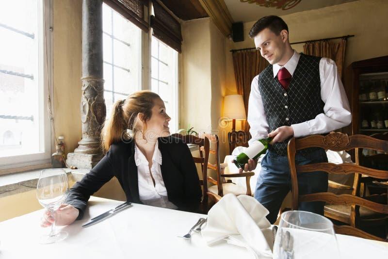 Camarero que muestra la botella de vino al cliente femenino en la tabla en restaurante imágenes de archivo libres de regalías