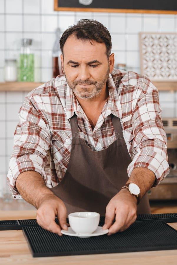 camarero que pone el café en contador de la barra imagen de archivo