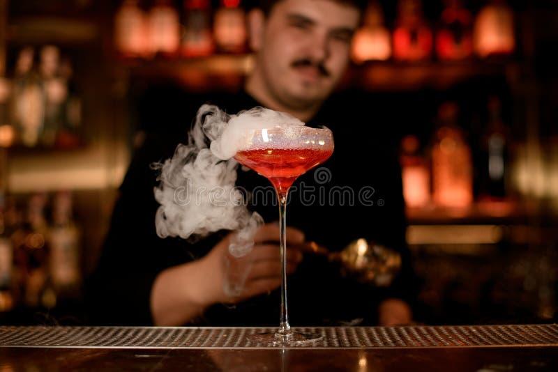 Camarero que pone espuma en una bebida del alcohol imagen de archivo