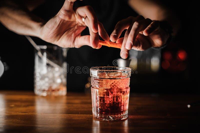 Camarero que prepara negroni alcohólico del cóctel del color rosado con hielo fotos de archivo libres de regalías