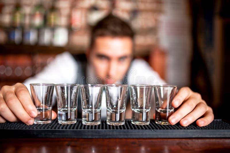 Camarero que prepara y que alinea los vasos de medida para las bebidas alcohólicas fotos de archivo libres de regalías