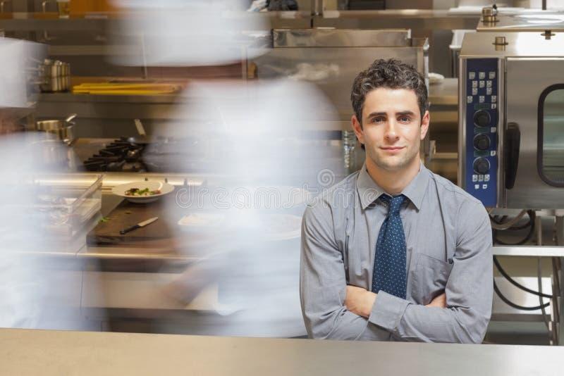 Camarero que se coloca en cocina ocupada fotos de archivo