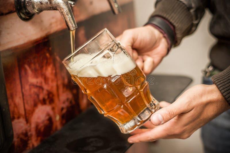 Camarero que se llena de una cerveza rubia del arte en un vidrio de la pinta imagen de archivo