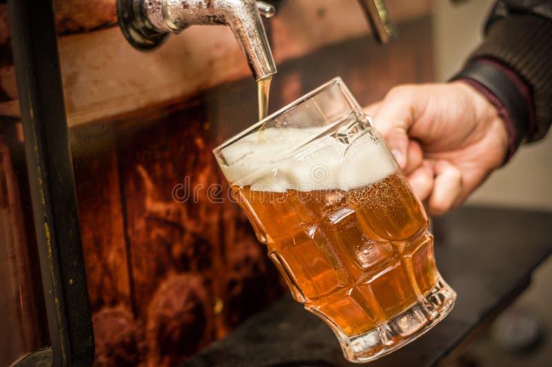 Camarero que se llena de una cerveza rubia del arte en un vidrio de la pinta foto de archivo