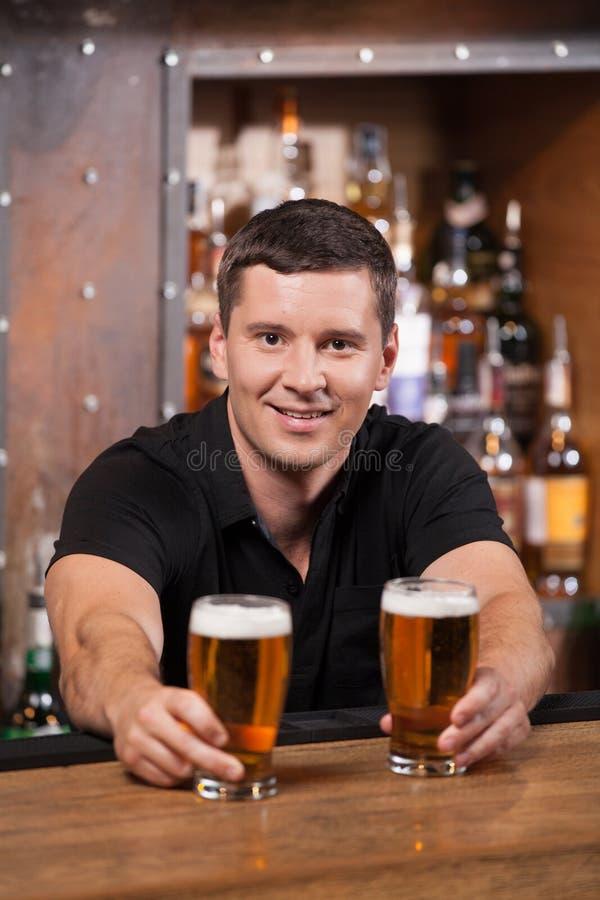 Camarero que sirve dos vidrios de cerveza fotos de archivo