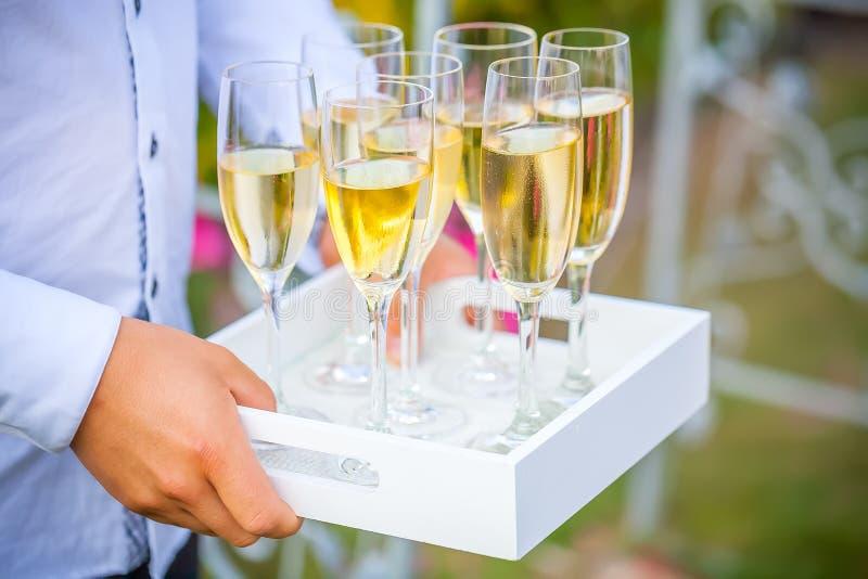 Camarero que sirve el champán de oro elegante en vidrios en la bandeja fotos de archivo