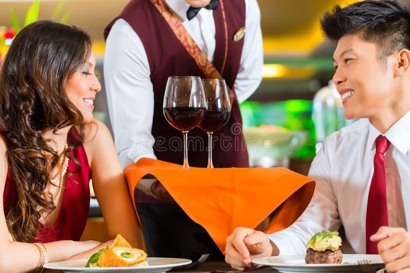 Camarero que sirve el vino chino de los pares imagenes de archivo
