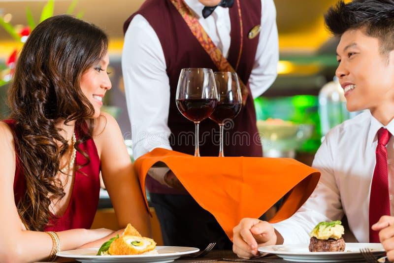 Camarero que sirve el vino chino de los pares foto de archivo