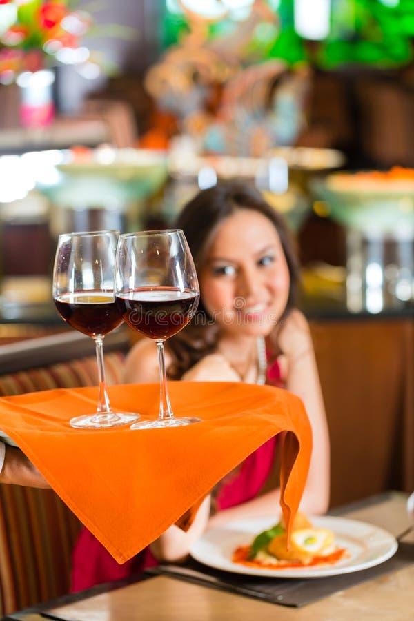 Camarero que sirve a mujer china el vino rojo imágenes de archivo libres de regalías