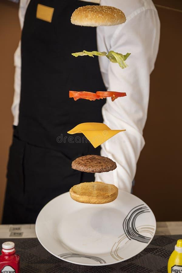 camarero que sirve una hamburguesa que vuela imagen de archivo libre de regalías