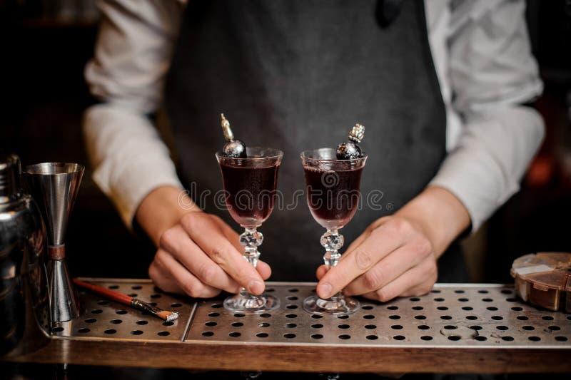 Camarero que sostiene dos cócteles red delicious en el contador de la barra foto de archivo libre de regalías