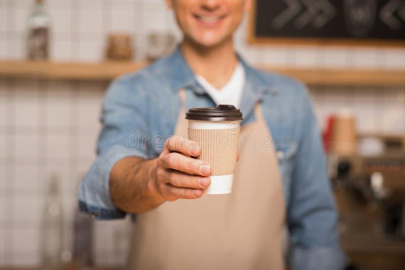 Camarero que sostiene el café para ir foto de archivo libre de regalías