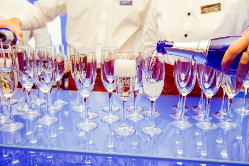 Camarero que vierte Champán de servicio personal en vidrios en soporte azul brillante Servicio en los eventos, reunión corporativ imagen de archivo