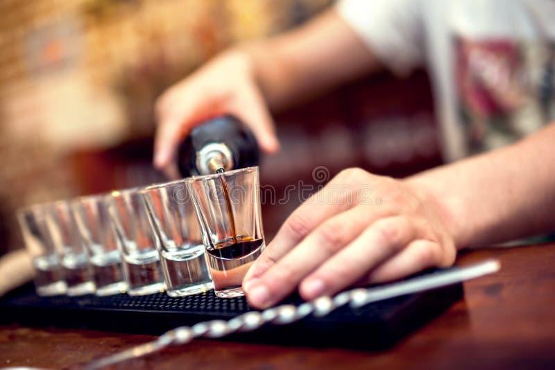 Camarero que vierte el cóctel alcohólico marrón en vidrios imagen de archivo libre de regalías