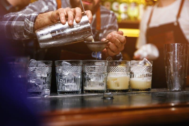 Camarero que vierte el cóctel sabroso en la tabla en club nocturno fotos de archivo