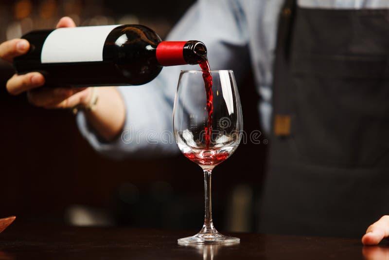 Camarero que vierte el vino rojo en la copa El Sommelier vierte la bebida alcohólica fotografía de archivo