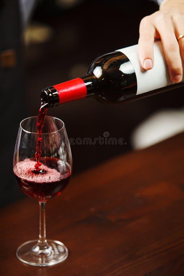 Camarero que vierte el vino rojo en la copa El Sommelier vierte la bebida alcohólica foto de archivo libre de regalías