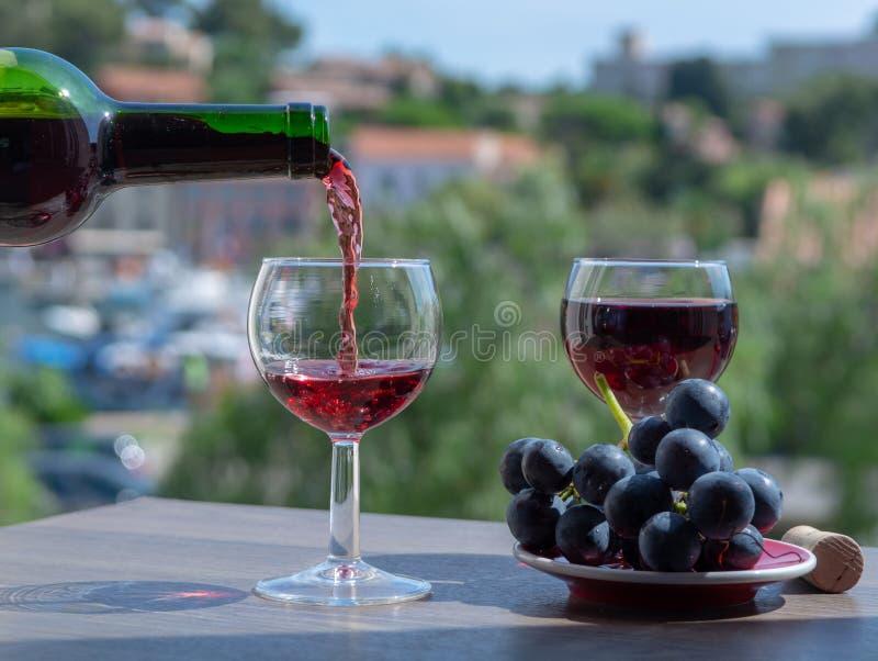 Camarero que vierte el vino rojo en terraza al aire libre del café foto de archivo libre de regalías