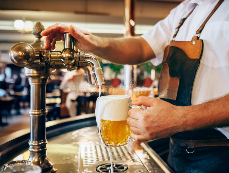 Camarero que vierte la cerveza fresca en una del pub tradicional checo imagenes de archivo