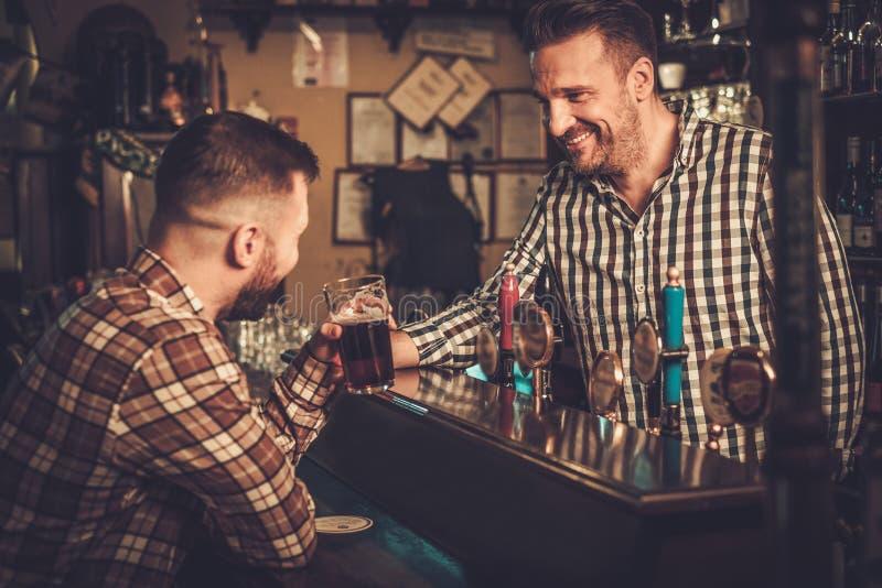 Camarero que vierte una pinta de cerveza al cliente en un pub fotografía de archivo libre de regalías