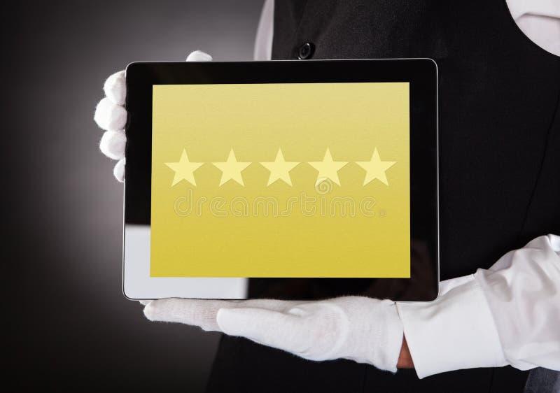 Camarero Showing Rating System en la tableta de Digitaces imagenes de archivo
