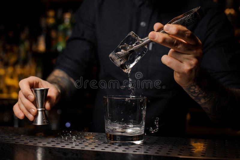 Camarero tatuado que pone un cubo de hielo en un vidrio de cóctel imagenes de archivo