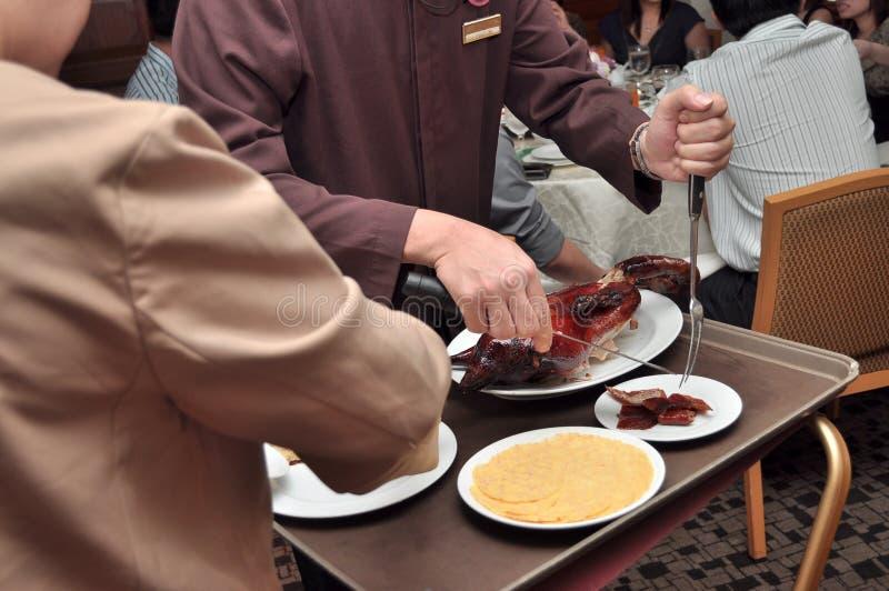 Camareros que sirven la comida en un restaurante imagen de archivo