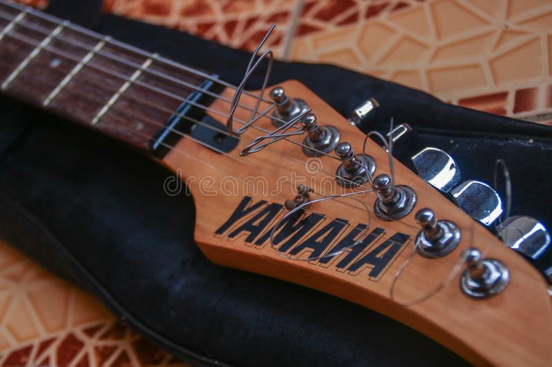 Yamaha 121D Electric Guitar. CAMARINES SUR / PHILIPPINES - FEBRUARY 3, 2019: Close up photo of the head of the Yamaha 121D Electric Guitar lying on the tiled royalty free stock photography