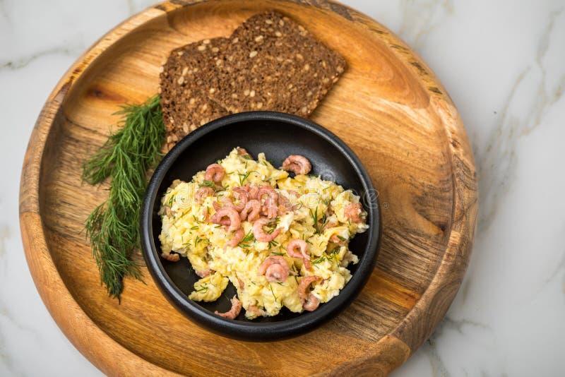 Camarones alemanes de Mar del Norte de Frisia con los huevos revueltos, el pan entero del grano y el eneldo en cuenco de madera e fotos de archivo