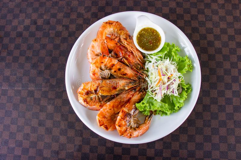 Camarones asados a la parrilla con los mariscos adornados con la salsa de inmersión picante vegetal y caliente en el plato de cer imagen de archivo