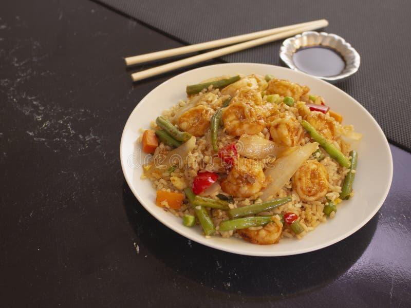 Camarones con estilo Cantonese del arroz y de las verduras en una placa blanca con la salsa de soja imagen de archivo