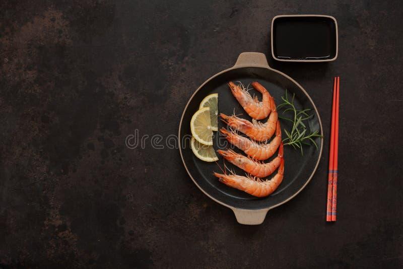 Camarones frescos en plato negro con la salsa del limón y de soja en estilo asiático con los palillos en fondo marrón fotografía de archivo libre de regalías