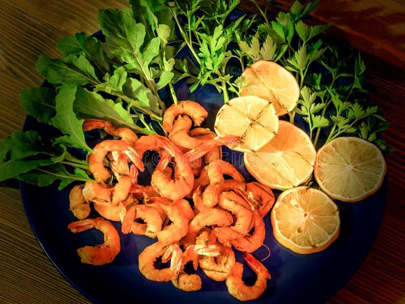 Camarones y lim?n asados a la parrilla con verdes, arugula y perejil en un plato azul foto de archivo libre de regalías