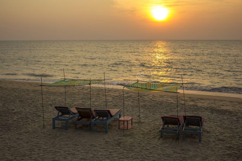 Camas azules vacías de la playa con los colchones rojos debajo de los toldos amarillos verdes en la arena amarilla contra el mar  imagenes de archivo